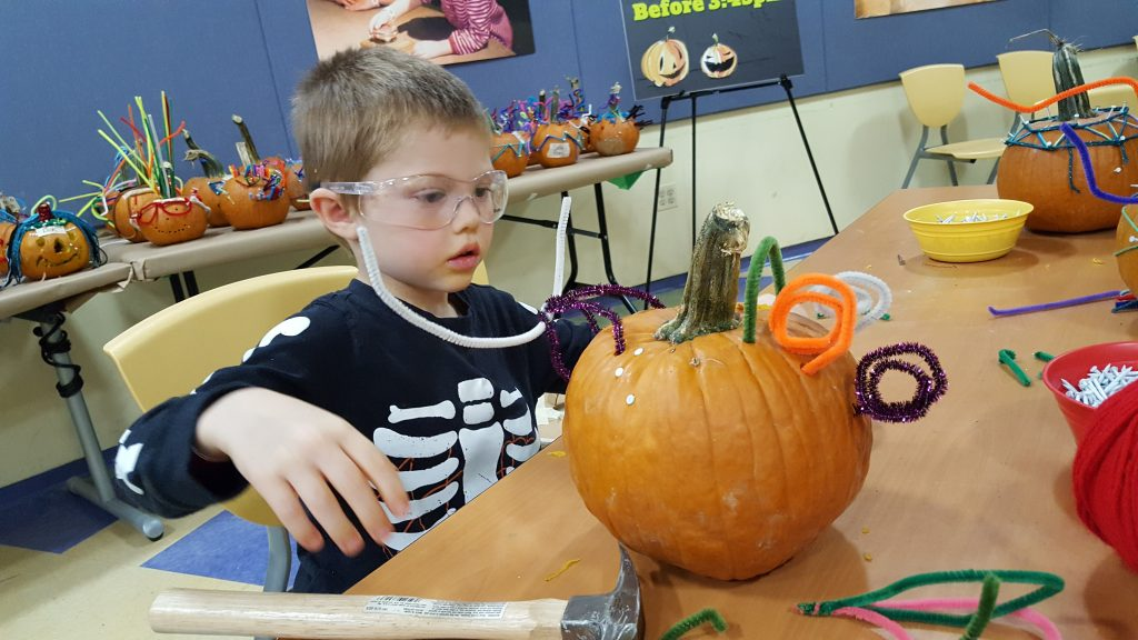Pounding nails and sticking pipe cleaners into a pumpkin