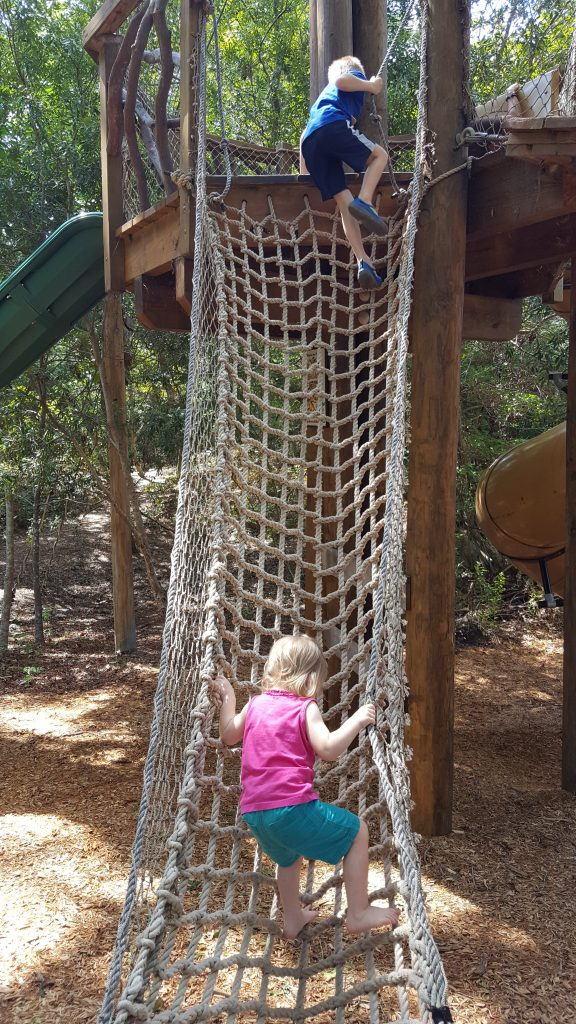 Harlan and Elise climb a cargo net.