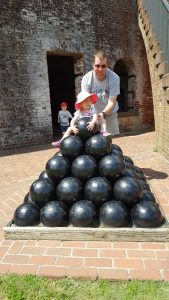 Elise sitting atop a stack of cannon balls at Fort Macon.