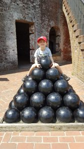 Harlan sitting on top of a stack of cannon balls at Fort Macon.