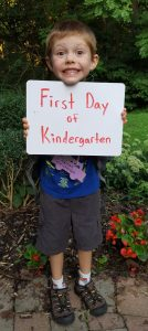 """Harlan holding a sign noting """"First Day of Kindergarten"""""""