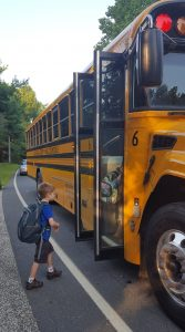 Harlan walking up to the open doors of school bus number 6.