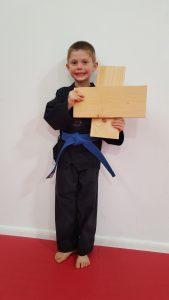 Blue Belt Harlan stands with his broken board.