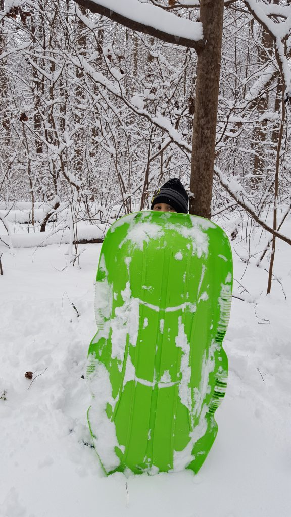 Harlan hiding behind a green sled.
